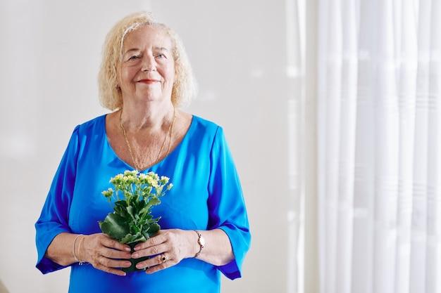 Mulher idosa com vaso de flores