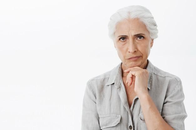 Mulher idosa complicada parecendo perplexa e descontente, pensando