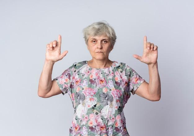 Mulher idosa confiante apontando para cima com as duas mãos isoladas na parede branca