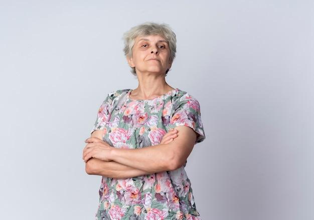 Mulher idosa confiante cruza os braços e parece isolada na parede branca