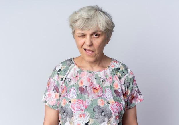 Mulher idosa confiante piscando o olho isolado na parede branca
