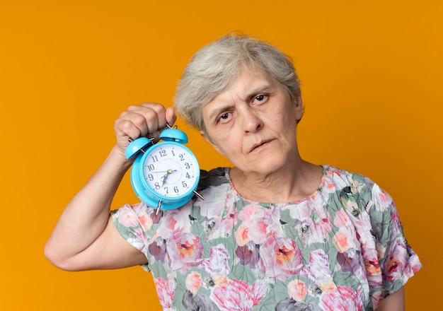 Mulher idosa confiante segurando o despertador isolado na parede laranja