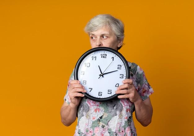 Mulher idosa confiante segurando um relógio olhando para o lado isolado na parede laranja