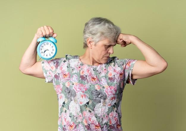 Mulher idosa confiante tensiona os bíceps e segura o despertador isolado na parede verde oliva