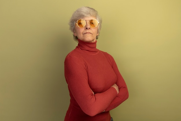 Mulher idosa confiante vestindo uma blusa de gola alta vermelha e óculos de sol em pé com a postura fechada em vista de perfil, isolada na parede verde oliva com espaço de cópia