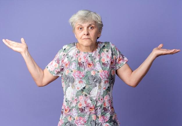 Mulher idosa confusa em pé com as mãos abertas, isoladas na parede roxa