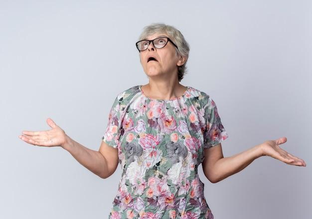 Mulher idosa confusa usando óculos ópticos de mãos abertas olhando para cima, isolado na parede branca