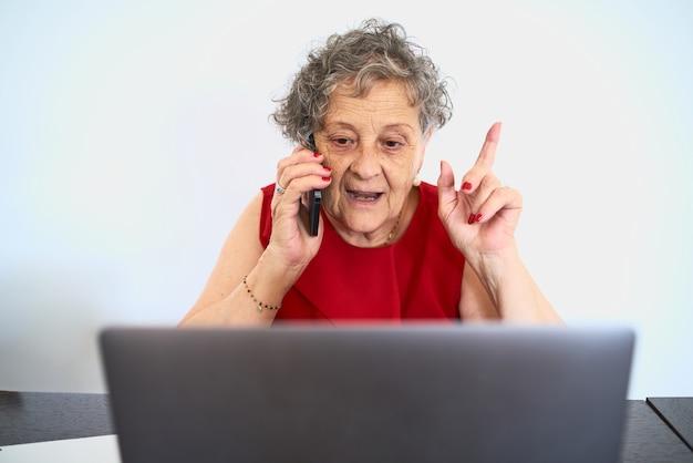 Mulher idosa conversando ao telefone enquanto usa o laptop na mesa do escritório em casa