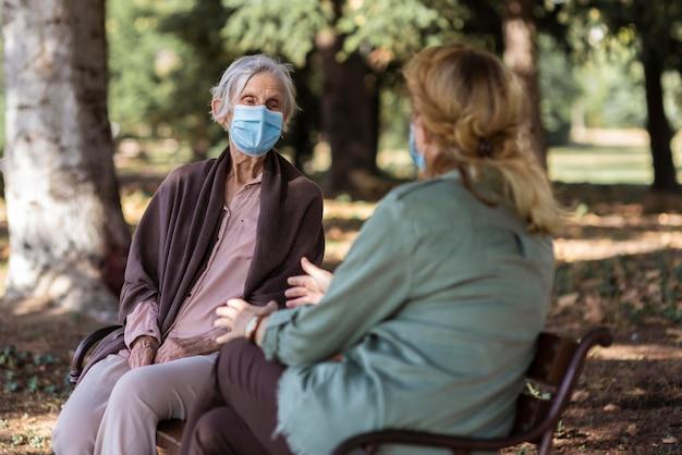 Mulher idosa conversando com alguém ao ar livre em uma casa de repouso