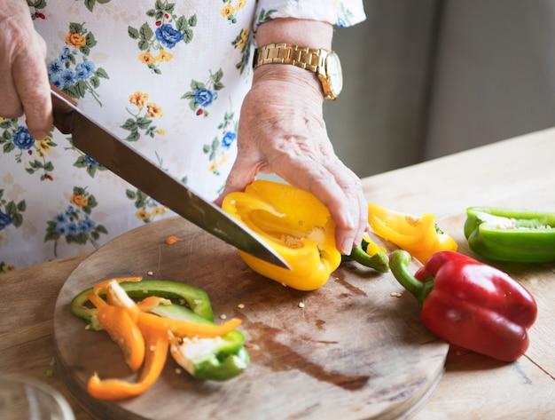 Mulher idosa, cortar, pimentões