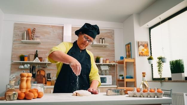Mulher idosa cozinheira polvilhando um pedaço de massa com farinha. padeiro sênior aposentado com bonete e uniforme polvilhando, peneirando, espalhando ingredientes refogados na massa, assando pizzas e pães caseiros.
