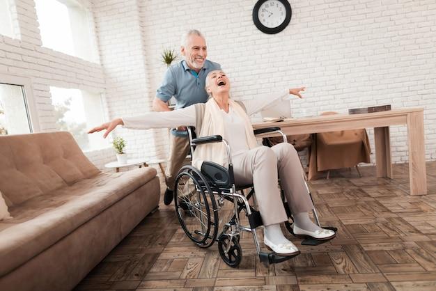 Mulher idosa cuidar do homem sênior em cadeira de rodas.