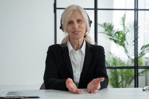 Mulher idosa de cabelos brancos falando para uma videochamada com câmera e seus parceiros de negócios