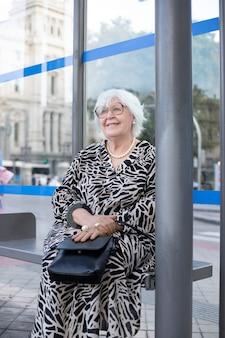 Mulher idosa de cabelos brancos no ponto de ônibus