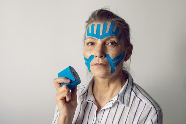 Mulher idosa de cabelos grisalhos com cinesiotapagem no rosto para suavizar
