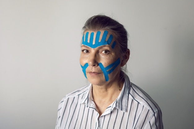 Mulher idosa de cabelos grisalhos com fita adesiva no rosto para suavizar