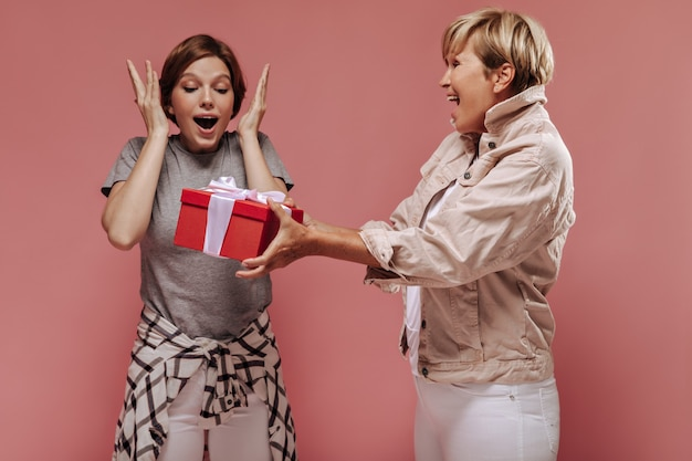 Mulher idosa de cabelos loira com jaqueta dando caixa de presente vermelha para garota emocionante com penteado curto e camisa xadrez em fundo rosa.