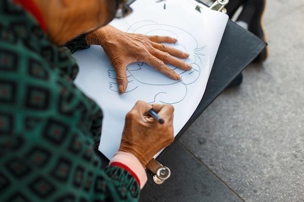Mulher idosa de óculos desenhando no papel