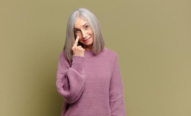 Mulher idosa de olho em você, sem confiança, observando e permanecendo alerta e vigilante