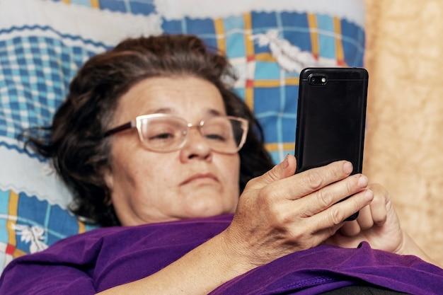 Mulher idosa deitada na cama durante a doença com um telefone nas mãos
