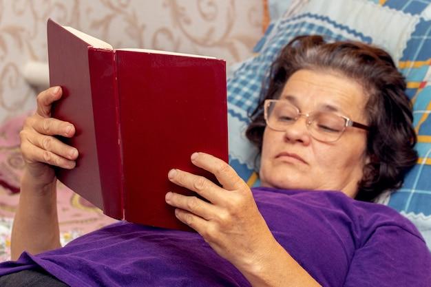 Mulher idosa deitada na cama lendo a bíblia, lendo um livro
