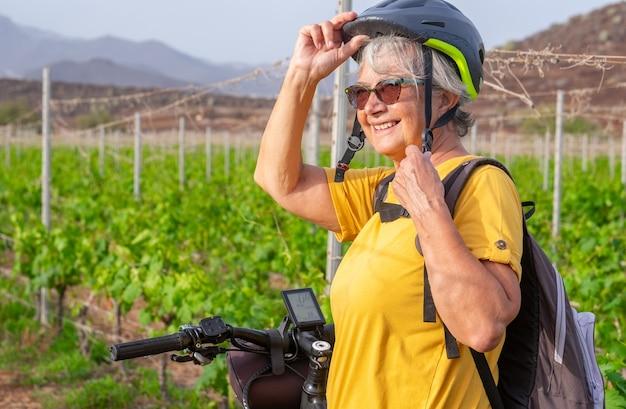 Mulher idosa dentro de um vinhedo com sua bicicleta elétrica, curtindo o ar livre e a natureza