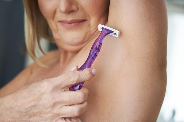 Mulher idosa depilando axilas no banheiro