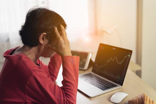 Mulher idosa deprimida e pensando seriamente em verificar a tabela de preços do bitcoin na bolsa digital no laptop