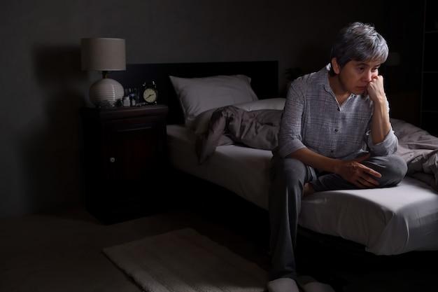 Mulher idosa deprimida sentada na cama não consegue dormir de insônia