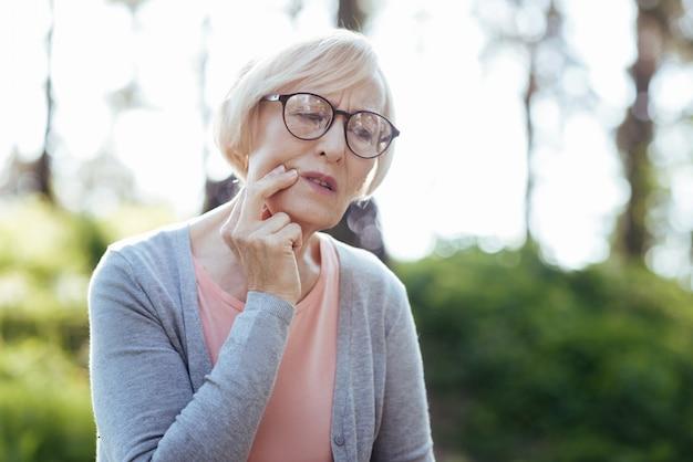 Mulher idosa deprimida tocando sua bochecha e sentindo dor enquanto está sentada no banco do parque