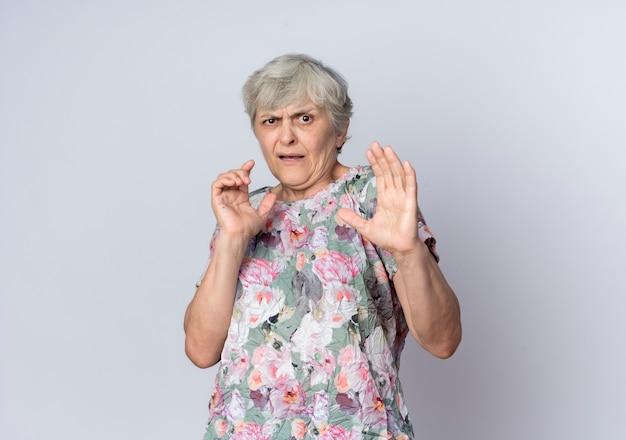 Mulher idosa descontente em pé com as mãos levantadas, isoladas na parede branca