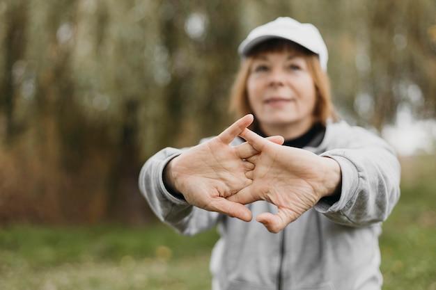 Mulher idosa desfocada esticando os braços ao ar livre