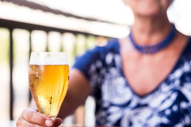 Mulher idosa desfocada sentada em um restaurante tomando um copo de cerveja congelada