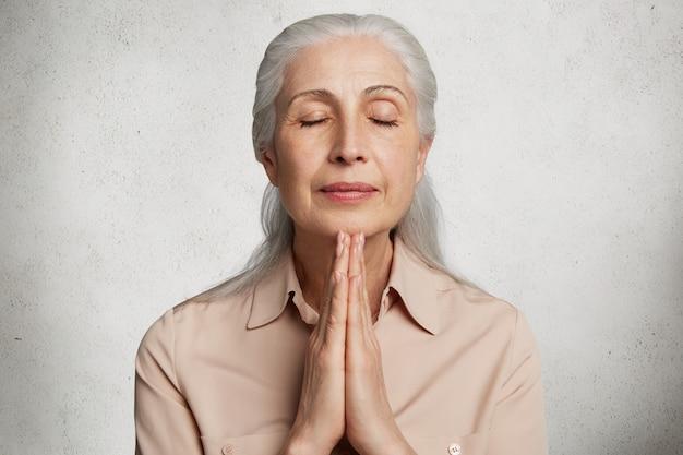 Mulher idosa deslumbrante contra parede de concreto