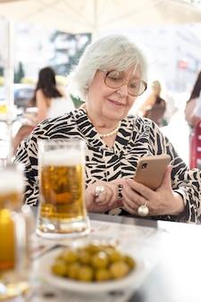 Mulher idosa digitando em seu telefone celular enquanto está sentada em um terraço bebendo uma cerveja