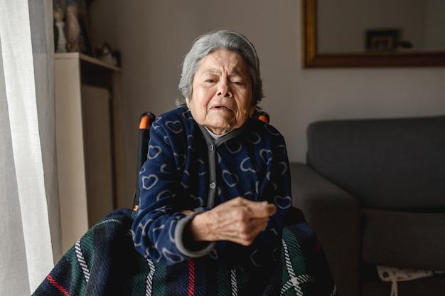 Mulher idosa do retrato sentada em uma cadeira de rodas em casa com o rosto confuso e desorientado ... terceira idade, conceito de assistência ao idoso em casa.