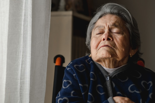 Mulher idosa do retrato sentada na cadeira de rodas em casa. idoso com olhos fechados e rosto confuso para perda de memória