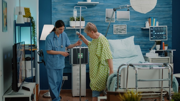 Mulher idosa doente caminhando com saco de gotejamento iv e enfermeira dando assistência
