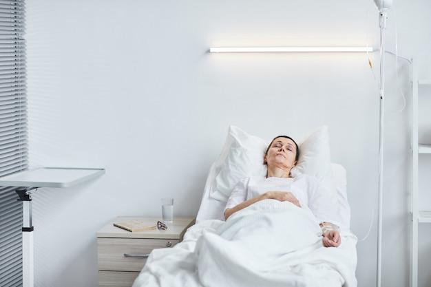 Mulher idosa doente deitada na cama após a operação no hospital
