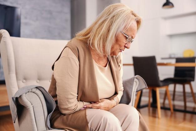 Mulher idosa doente sentada em casa em sua cadeira e segurando a barriga