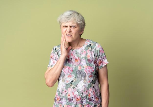 Mulher idosa dolorida coloca a mão no queixo isolado na parede verde oliva