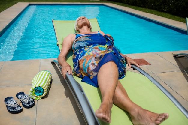 Mulher idosa dormindo em uma espreguiçadeira à beira da piscina