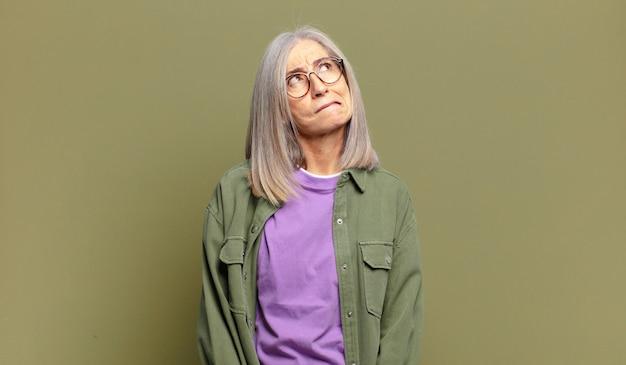 Mulher idosa duvidando ou pensando, mordendo o lábio e sentindo-se insegura e nervosa, procurando copiar o espaço ao lado