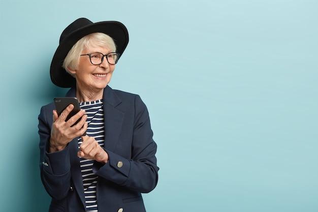 Mulher idosa e atraente digita mensagem de texto no celular, usa novo aplicativo online, tem expressão facial positiva, desvia o olhar, usa capacete e casaco elegantes, fica de pé sobre a parede azul, espaço livre
