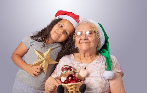 Mulher idosa e criança com chapéu de natal e enfeites de natal nas mãos em cinza
