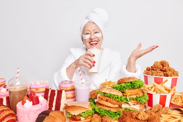 Mulher idosa e despreocupada bebendo refrigerante rodeada de junk food