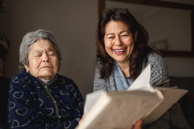 Mulher idosa e doente com perda de memória. filha sorridente, mostrando um álbum de fotos.