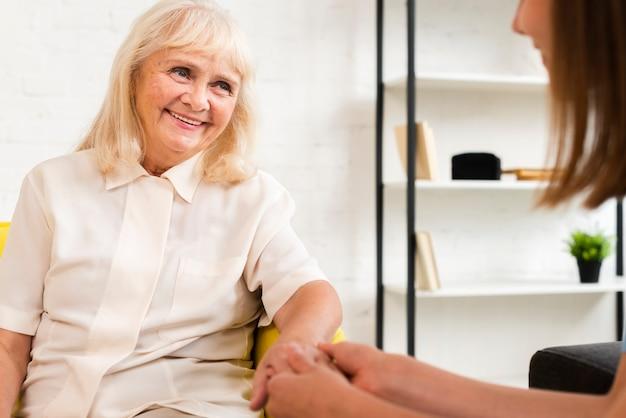 Mulher idosa e enfermeira de mãos dadas