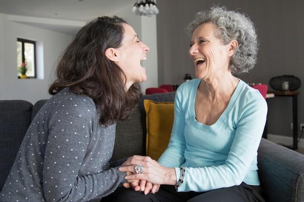 Mulher idosa e filha rindo e de mãos dadas