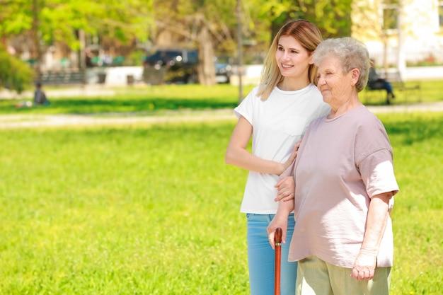 Mulher idosa e jovem cuidador no parque em dia ensolarado